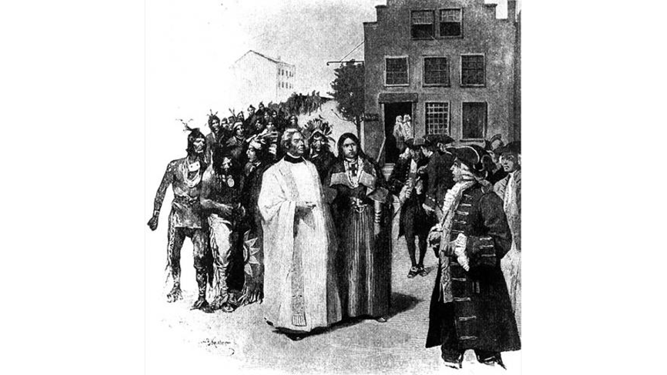 A woman in Native American clothing and a man in clerical robes enter a colonial town accompanied by a group of Native Americans.